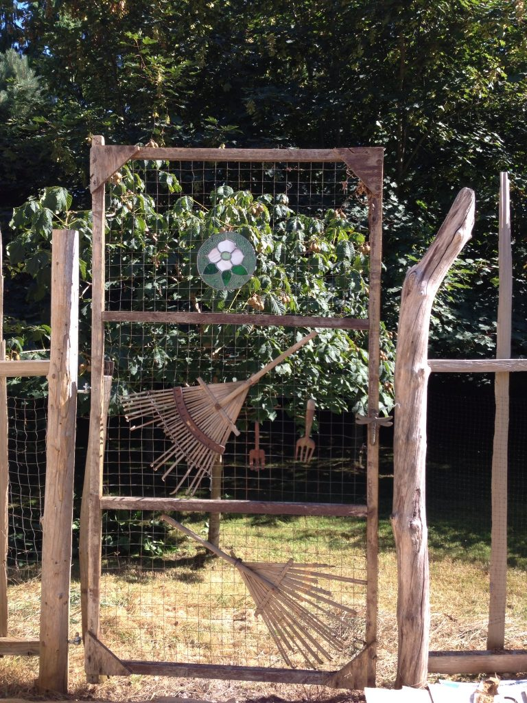 Gate made from repurposed screen and random objects.